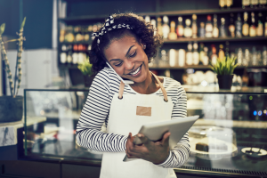 Smiling entrepreneur standing in front of the counter of her cafe talking on a cellphone and using a tablet